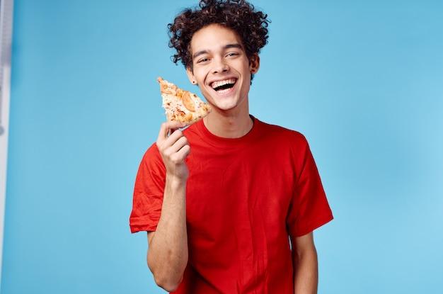Gelukkige kerel met plak van pizza op blauwe achtergrond, krullend haar emoties bijgesneden weergave