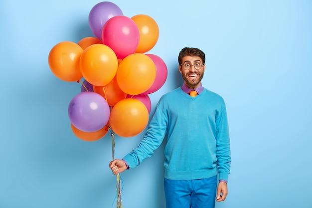 Gelukkige kerel met verjaardagshoed en ballonnen poseren in blauwe trui