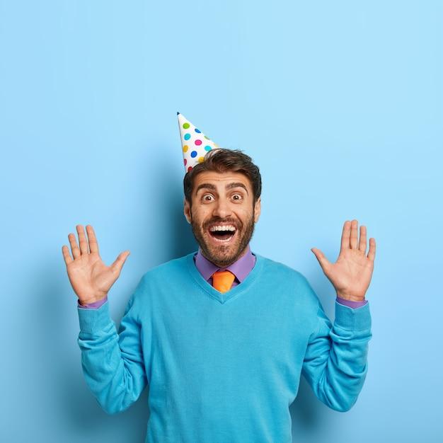 Gelukkige kerel met verjaardagshoed poseren in blauwe trui
