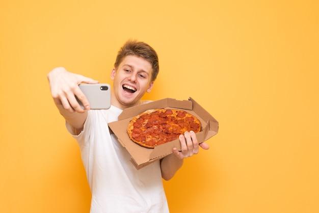 Gelukkige kerel neemt selfie met een doos pizza op een geel