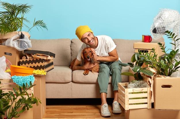 Gelukkige kerel omhelst favoriete hond omringd door dozen