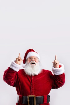Gelukkige kerstman, die in witte muur omhoog wijst