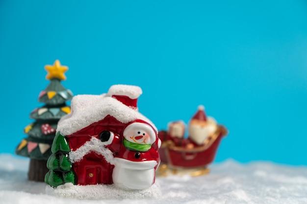 Gelukkige kerstman met giftendoos op de sneeuwslee die naar sneeuwhuis gaan.