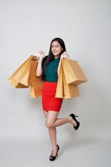 Gelukkige kerstmis aziatische vrouw het winkelen holdingsdocument zakken