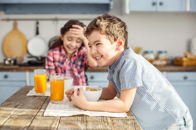 Gelukkige kinderen. aantrekkelijke waakzame donkerharige jongetje lachen en gezond ontbijten met zijn zus en het meisje lachend in de