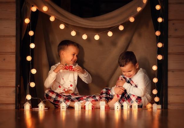 Gelukkige kinderen bij de kerstboom hebben plezier in het nieuwe jaar