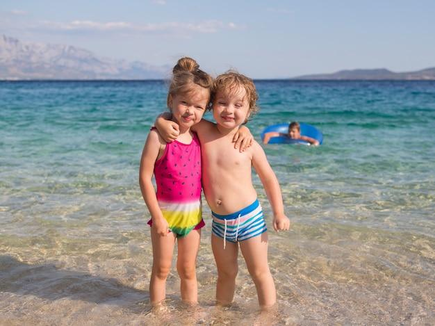 Gelukkige kinderen, broer en zus, knuffelen op het strand, kroatië, adriatische zee