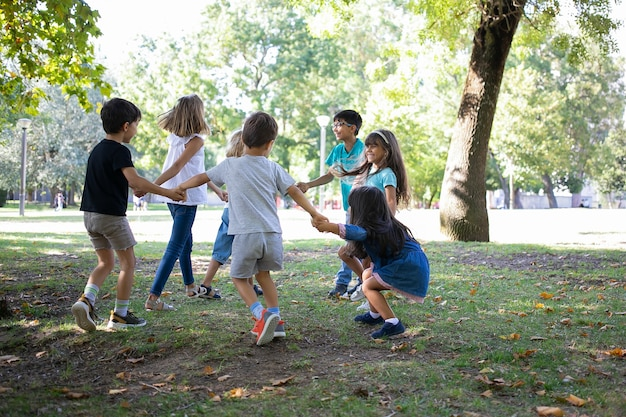 Gelukkige kinderen buiten samen spelen, dansen op gras, genieten van buitenactiviteiten en plezier maken in het park. kinderfeestje of vriendschapsconcept