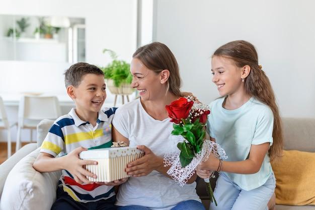 Gelukkige kinderen cadeau geven een bloemen aan moeder. gelukkige moederdag! kinderen jongen en meisje feliciteren glimlachende moeder, geven haar bloemen boeket rozen en een geschenkdoos tijdens vakantieviering