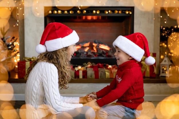 Gelukkige kinderen dichtbij open haard met kerstmis. kinderen hebben plezier thuis.