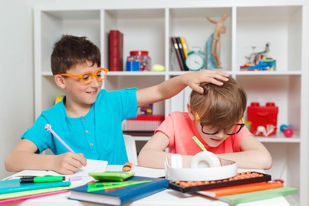 Gelukkige kinderen die aan bureau zitten en huiswerk doen.