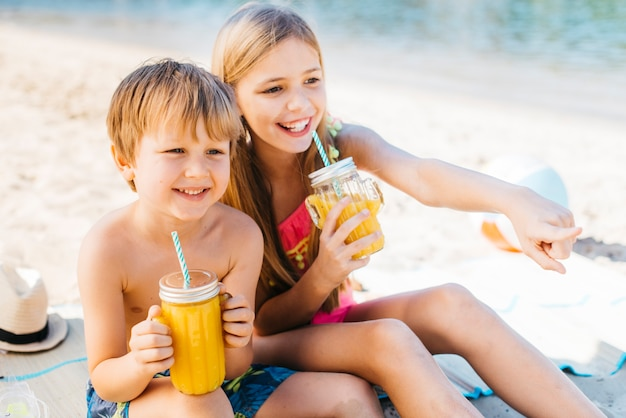 Gelukkige kinderen die met drank op kust glimlachen