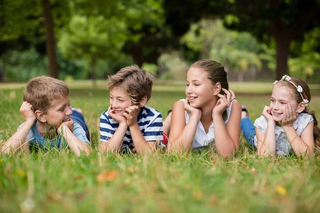 Gelukkige kinderen die met elkaar in wisselwerking staan terwijl het liggen op gras