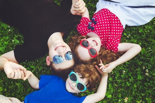 Gelukkige kinderen die op de handen van de grasholding liggen.