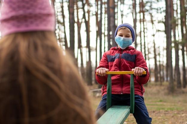 Gelukkige kinderen die op de schommel slingeren en medische maskers dragen ter bescherming tegen de gevaarlijke ziekte van covid-19