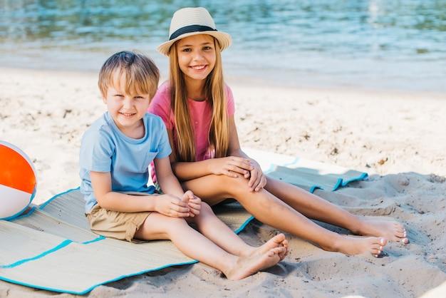 Gelukkige kinderen die op kust glimlachen