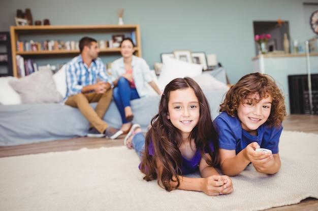 Gelukkige kinderen die op tapijt liggen terwijl ouders