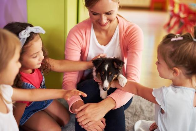 Gelukkige kinderen die schattige hond aaien