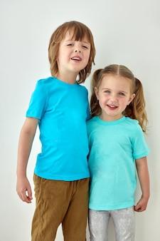 Gelukkige kinderen in blauwe t-shirts witte muur