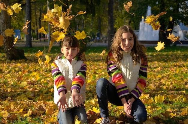 Gelukkige kinderen in de herfstpark, actieve jonge geitjes die pret hebben en met gele bladeren in openlucht spelen