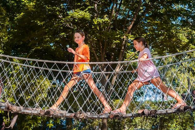 Gelukkige kinderen in de speeltuin. het oversteken van een houten brug