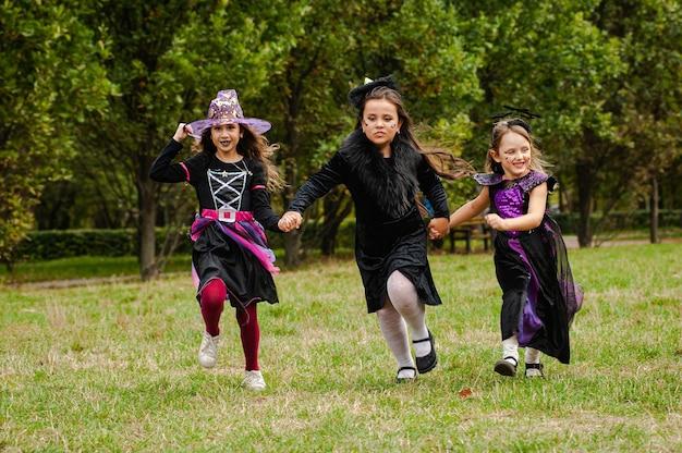 Gelukkige kinderen in halloween-kostuums die op het gazon lopen