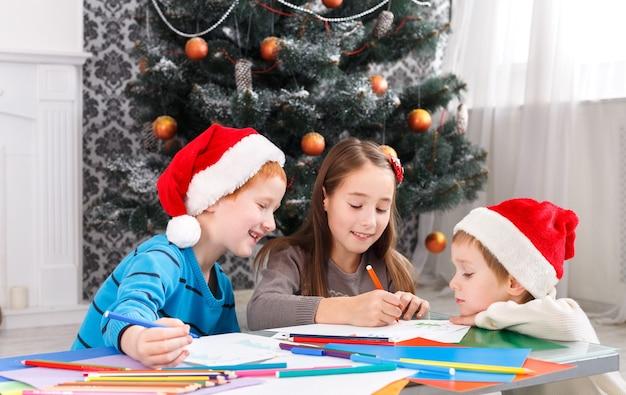 Gelukkige kinderen in kerstmutsen maken een verlanglijstje met kerstcadeautjes