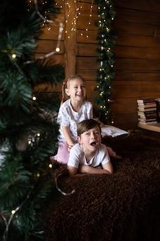 Gelukkige kinderen in pyjama spelen op kerstochtend in de buurt van de kerstboom