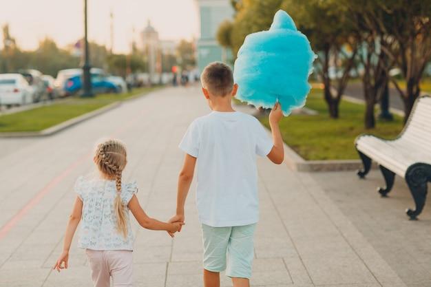 Gelukkige kinderen jongen en meisje blauwe suikerspin buitenshuis eten.