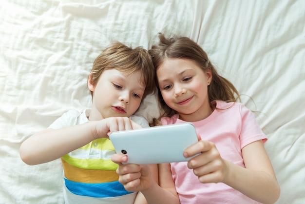 Gelukkige kinderen kijken naar online film met digitale mobiele telefoon en thuis op bed liggen