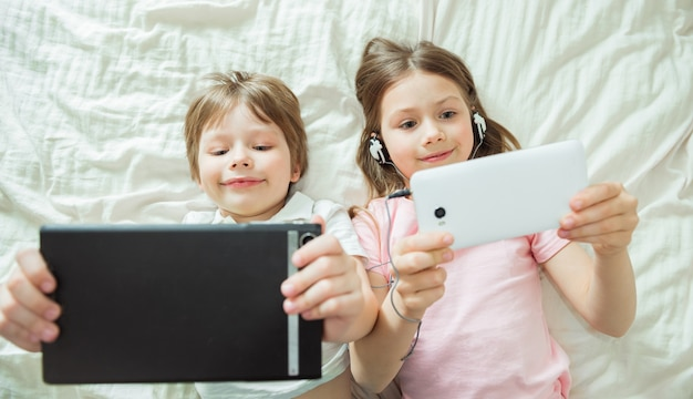 Gelukkige kinderen kijken naar online films met digitale tablets en thuis op bed liggen