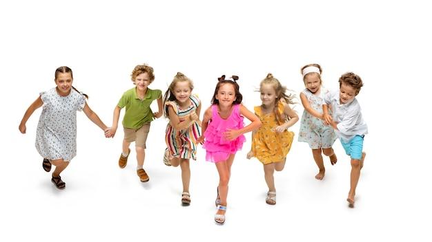 Gelukkige kinderen, kleine en emotionele blanke kinderen springen en rennen geïsoleerd op een witte achtergrond. ziet er gelukkig, vrolijk, oprecht uit. copyspace voor advertentie. jeugd, onderwijs, geluk concept.