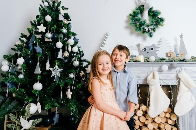 Gelukkige kinderen knuffelen en lachen in de studio met cristmas boom en winter vakantie decoraties.
