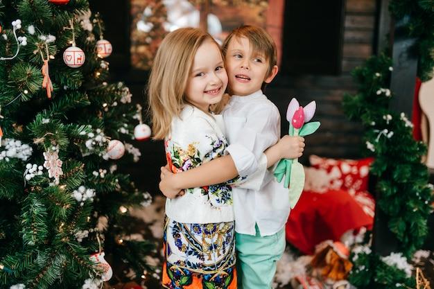 Gelukkige kinderen knuffelen in de studio met kerstboom en nieuwjaar decoraties.