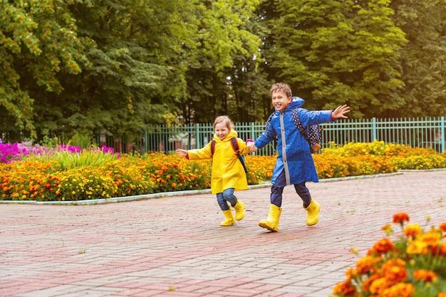 Gelukkige kinderen lachen, rennen en rennen naar school gekleed in regenjassen
