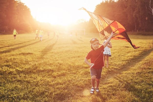 Gelukkige kinderen lanceren een vlieger in het veld bij zonsondergang. kleine jongen en meisje op zomervakantie