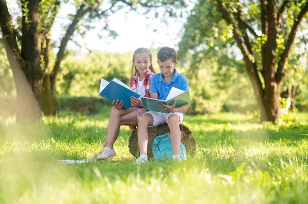 Gelukkige kinderen lezen in het park op zonnige dag