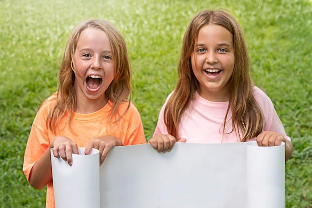 Gelukkige kinderen met een wit bord voor reclame op een achtergrond van gras.