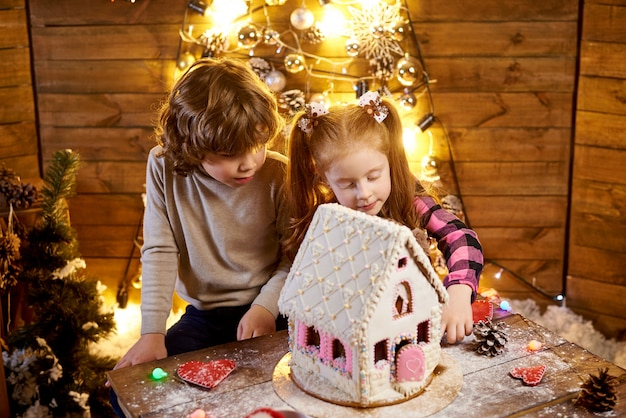 Gelukkige kinderen met kerstpeperkoek in een ingerichte kamer voor de vakantie.