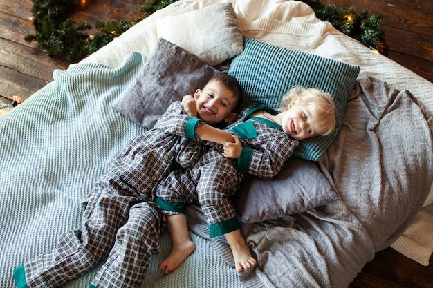 Gelukkige kinderen op bed te wachten op het nieuwe jaar
