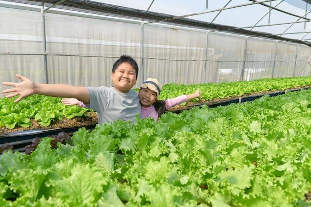 Gelukkige kinderen presenteren met de hand aan biologische plantaardige boerderij