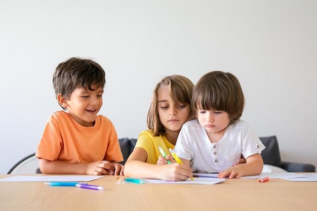 Gelukkige kinderen schilderen met markeringen in de woonkamer. mooie kleine jongens en blond meisje zittend aan tafel, tekenen op papier met pennen en thuis spelen. jeugd, creativiteit en weekendconcept