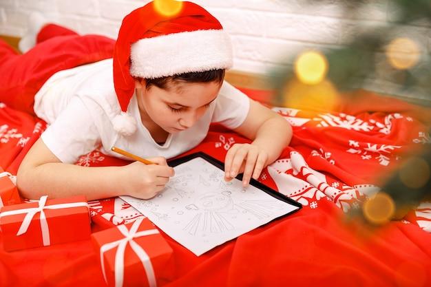 Gelukkige kinderen schrijven brief aan de kerstman in de buurt van de kerstboom