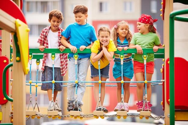 Gelukkige kinderen spelen en lachen op speelplaats