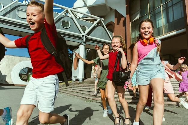 Gelukkige kinderen spelen in de stad straat in zonnige zomerdag voor modern gebouw. groep gelukkige kinderen of tieners die samen plezier hebben. concept van vriendschap, jeugd, zomer, vakantie.