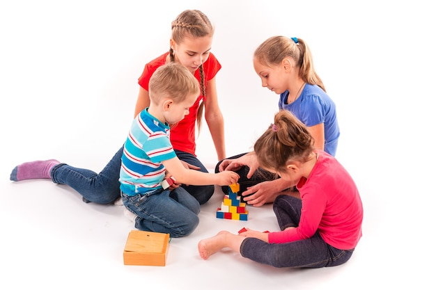 Gelukkige kinderen spelen met bouwstenen geïsoleerd op wit. teamwerk, creativiteit concept.