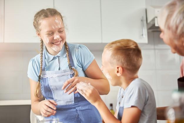 Gelukkige kinderen spelen met meel in de keuken van hun grootmoeder