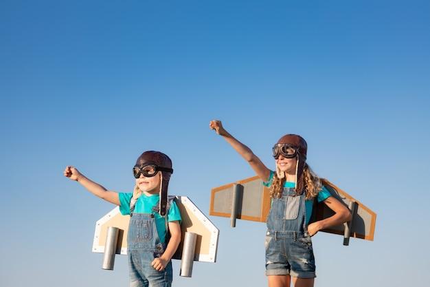 Gelukkige kinderen spelen met speelgoed vleugels tegen zomer hemelachtergrond. kinderen hebben plezier buiten.