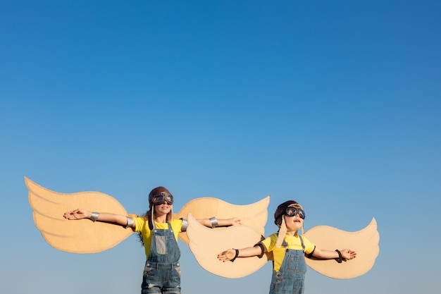 Gelukkige kinderen spelen met speelgoed vleugels tegen zomer hemelachtergrond