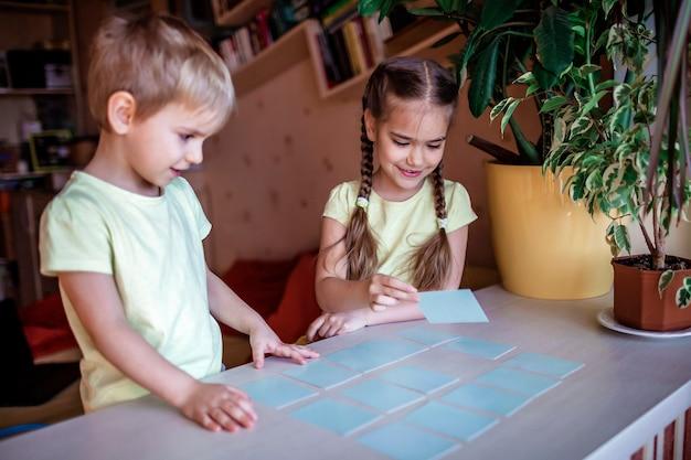 Gelukkige kinderen spelen op bordspel memo in huiselijk interieur, gezinswaarden eigenlijk, thuis blijven, leven tijdens quarantaine